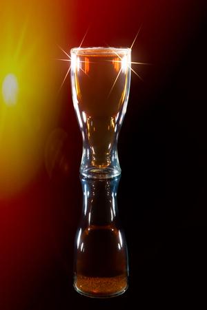 スポット ライトの下でビール賞を受賞。ラガーはビールの国際デーのパイント ガラスを型ボトルで飲みます。スポット ライトとレンズ フレアの黒 写真素材