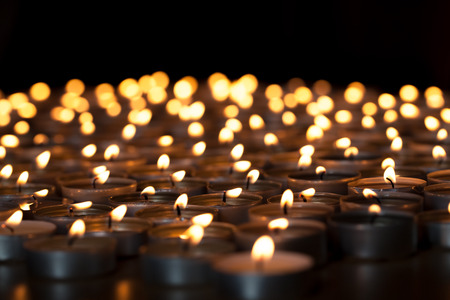 Flaming candles. Spiritual image of tealights providing sacred light. Romantic candlelight at night. A spread of lit wax candles against black background with copy space. Stock Photo