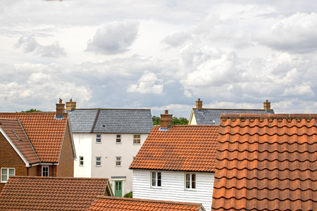 Real estate. Suburban property roof tops on a modern contemporary housing estate. Mixed residential building types. Stock Photo