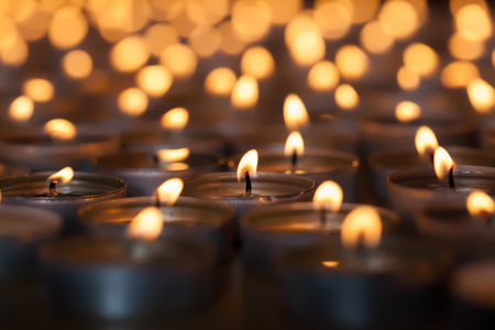 Lighted candle amongst hundreds of flaming tea light candles. Beautiful romantic candlelight. Selective focus on central lit wick. Stock Photo