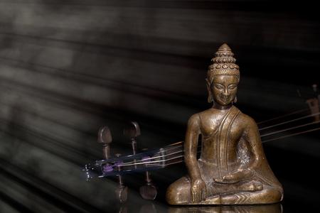éxtasis: Espiritual, New Age y música religiosa. Buda de bronce meditando con el violín contemporáneo en el rayo divino de la luz. Música clásica tradicional.