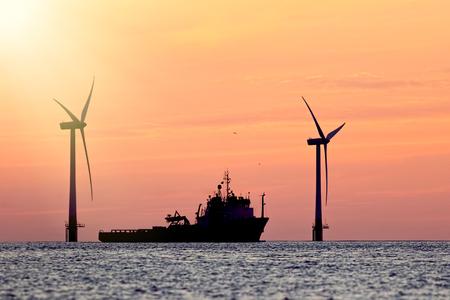 Risorse sostenibili Parco eolico con la siluetta della nave all'alba o al tramonto tropicale. Energia solare ed eolica e approvvigionamento alimentare rappresentati in questa immagine tranquilla con lo spazio della copia.