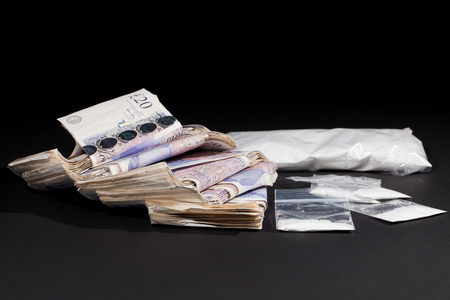 UK drug money. Cocaine and cash. Money from drug dealing in Great Britain. Thousands of pounds in bank notes and bags of white powder.