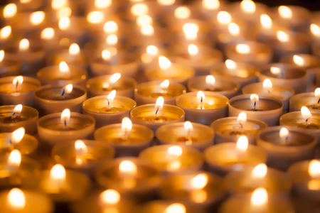 Soft dreamy image of bright candlelight from burning tea light candles. Christmas background image. The romantic glow of yellow flames. Stock Photo
