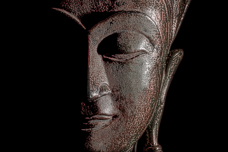 Buddha head. Modern buddhism in focus. Bronze statue face in close up. Against black background with copy space.