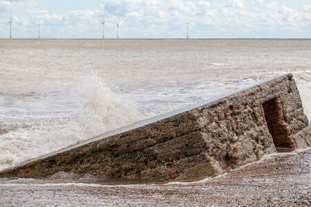 reclamation: Coastal erosion and rising sea level reclaiming a WW2 anti-invasion beach defence building on the East Coast of England. World War 2 concrete coastal invasion structure.  Stock Photo