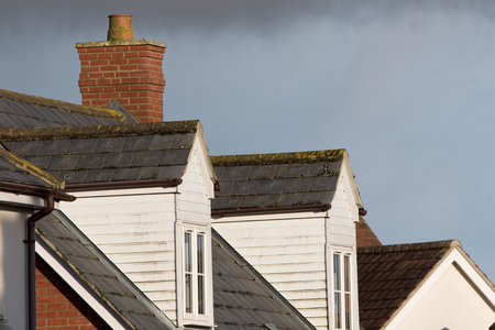 Dormer roof windows. Loft structures on modern town house buildings. White cladding and slate tiles on dormer windows.