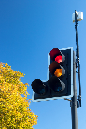 stop and go light: British road traffic light with signal on red and amber. Lights with traffic sensor against blue sky with copy space.
