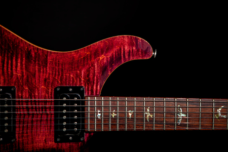 Beautiful red electric guitar against black background. Quality musical instrument with flame maple top and bird inlays on neck fingerboard.