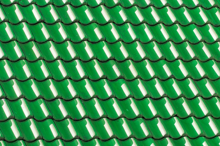 is green: Green house roof tiles. Geometric pattern background image. Light and shade on vibrant colored curved tiles. Stock Photo