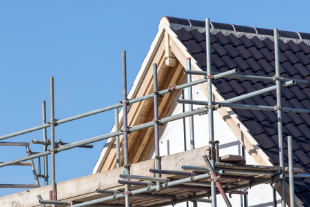 round: Modern house roof construction with scaffold pole platform. New build domestic building.