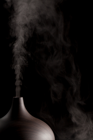 Alternative medicine. Aromatherapy essential oil diffuser device working. Close up in use against black background. Stock Photo
