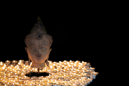 Enlightenment. Spiritual image of serene buddha head illuminated by tealight candles. Beautiful Buddhism image with black background and copy space. Stock Photo