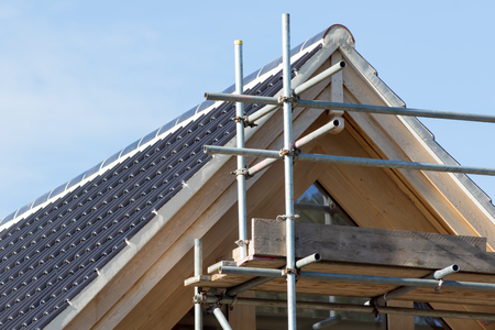 Modern house roof construction. Black curved ceramic tiles with scaffolding on the front of an expensive new build home. Stock Photo