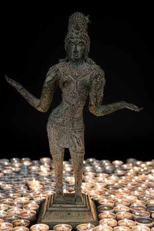 Lakshmi Hindu Goddess of wealth, fortune, fertility and prosperity with Festival of Light candles. Traditional bronze statue. Hinduism diety. Stock Photo