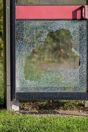 antisocial: Vandalism with smashed glass on British telephone box. Broken glass caused by anti-social behaviour.