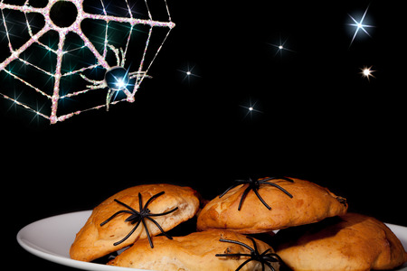 Fun Halloween spider food. Trick or treat spooky party snacks with fantasy cartoon style creepy background. Novelty plastic spiders on cookie muffins with sparkling spider web over a night sky with stars. Stock Photo