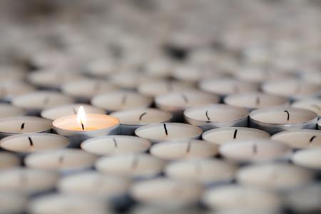 Licht schijnt van een eenzame brandende kaarsvlam. Selectieve focus op een vlammend theelichtje onder veel gedoofde kaarsen. Stockfoto