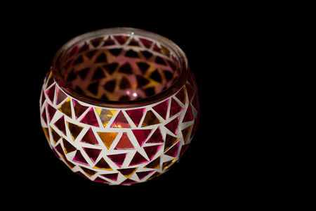 Simple traditional art and craft tealight candle holder. Decorative bowl with triangles of colored cut glass stuck together. Black background with copy space.