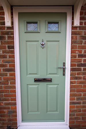 Green door. Modern house composite upvc front door with chrome hardware. Timber look classic design.