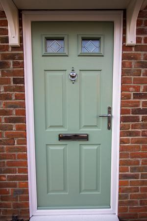 Green door. Modern house composite upvc front door with chrome hardware. Timber look classic design.