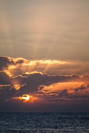 Autumnal sunrise sky. Rays of orange sunlight over the sea at dawn. Spiritual image as a new day begins. Stock Photo