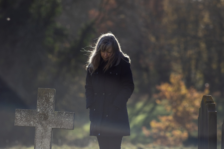 Living with grief and mortality. Thinking lady mourns at old grave cross in cemetery. Sadness at death and mortality by middle-aged to elderly woman dressed in black with head bowed. 스톡 콘텐츠