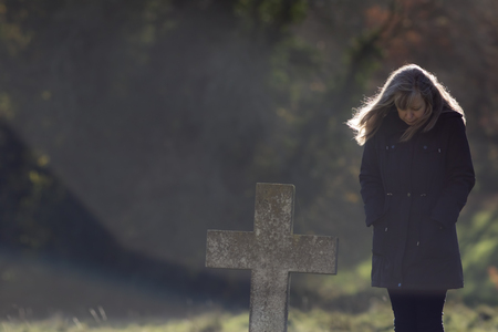 Respect for the dead. Mourning woman with head bowed  in cemetery. Middle-aged grieving lady dressed in black standing by grave. Old stone headstone. With copy space.