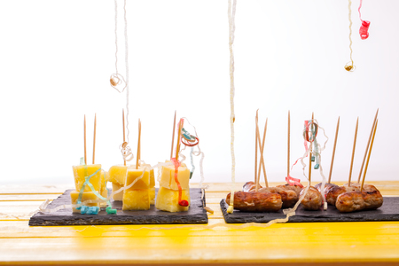 Remains of party food nibbles. Leftover cocktail sausages and cheese and pineapple on sticks with streamers close up against white background.
