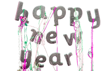 Happy new year written in silver glitter party text with party popper streamers. New year's eve image. Studio set against a bright white background.