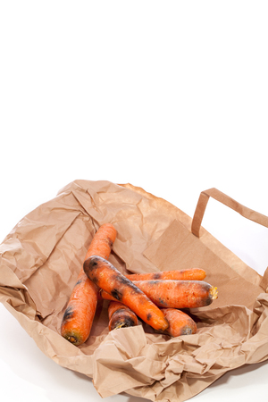 Rotten carrots on supermarket bag. Mouldy vegetables as wasted food. Black carrots past best before date. White background with copy space.