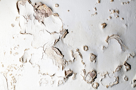 Blown plaster. Damp salt damaged wall suface in need of repair. Close up image of old bubbled flaking plaster coat.