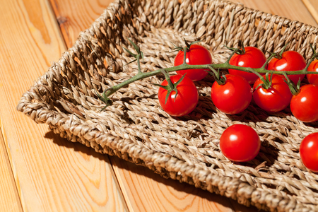 Red cherry vine sun-ripened piccolo tomatoes in wicker basket tray. Healthy sweet red organic miniature tomato stem.