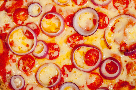Pizza background. Close-up of melted cheese red onion and tomato. Mouth-watering multi-colored home-made Italian comfort food with vivid colors and textured aesthetic pattern.