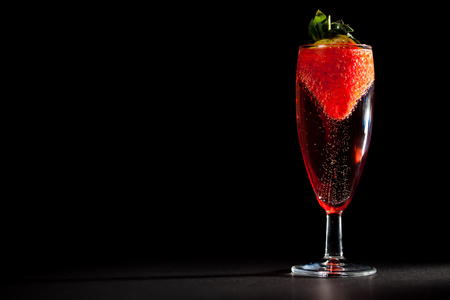 Celebration drink. Glass of sparkling pink Champagne wine with strawberry. Perfect Valentines or anniversary indulgence. Black background with copy space. Stock Photo