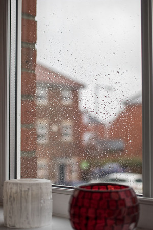 Rainy day. View through rain water drops on house window. Raindrops on glass window pain. Depressing weather and staying indoors.