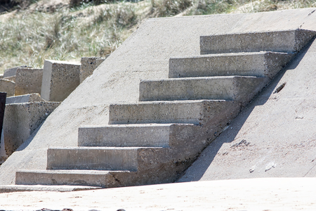 Concrete steps of an old sea defence barrier now leading to nowhere at a beach cliff edge