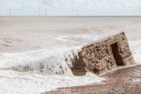 Coastal erosion. Wave action engulfing WW2 concrete ant-invasion structure. War building uncovered on the beach. Stock Photo