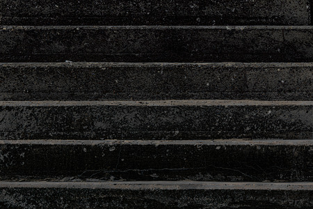 Death. Conceptual high-contrast image of charred black concrete steps. Abstract high contrast graphic close-up of the horizontal lines of coarse dark man-made steps. Path to hell.