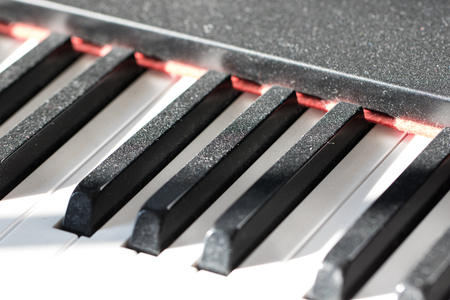 Dust on piano keys showing a lack of practice. Reluctant musician concept image showing dusty keyboard as evidence for a lack of musical instrument practise time. Stock Photo