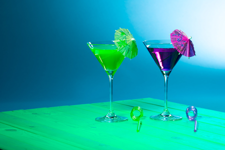 Exotic cocktail drinks. Summer vacation beach party alcohol. Fun green and purple cocktails with paper umbrellas and curly straws against graduated blue background.