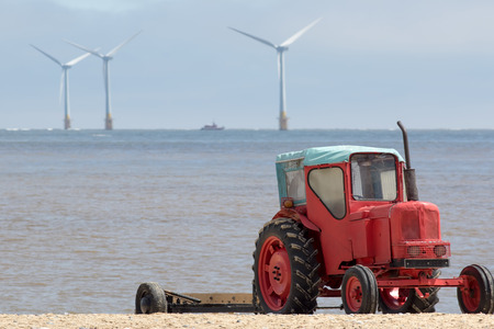 The future of energy production and environmental conservation represented by quirky red diesel beach tractor with offshore clean energy and sustainable resource wind farm turbines in the distance.
