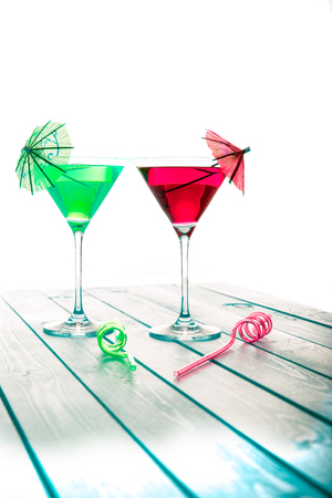Summer fun alcoholic and non-alcoholic green and red fruit cocktail drinks. Party cocktails for the sophisticated party-goer. Cocktail glass, decorative umbrella and curly straw to match!