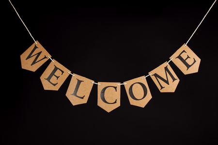 Welcome home banner. Greeting letters hanging on bunting. Welcoming text on string against black background.
