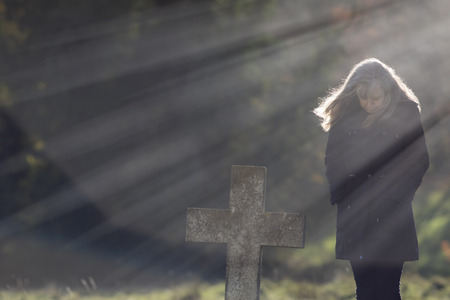 Divine light. Heavenly rays of sunshine behind grieving widow in cemetery. Mourning lady contemplating life and death by the stone cross of a grave.