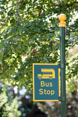 Rural bus stop sign in close-up. Yellow and green countryside vintage bus stop post.