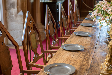Medieval dining table and chairs. Mediaeval period banquet table set with metal plates. Fine historic fraternal banqueting hall. Secret society chamber with anonymous empty seats.
