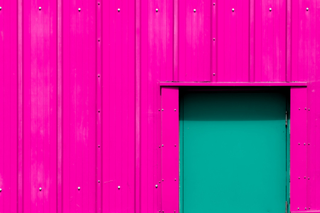 Neon pink building with green door. Vibrant paint color choice. Colorful gaudy exterior panelled wall representing modern industrialism. Imagens - 107740021