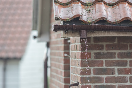 Broken gutter missing a downpipe. House guttering repair leaking rain water. Drainage problem with brown UPVC pipe. Reklamní fotografie