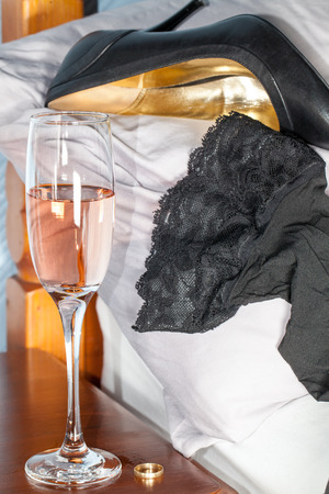 Extramarital affair.   Sexy black stockings and leather stiletto heel shoe on a bed next to pink champagne alcohol and a wedding ring. One night stand adultery.